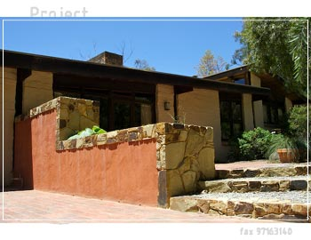 Earthy wall with terracotta render and castlemaine rock capping